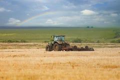 Trattore che ara il campo per la piantatura in un Sunnyday Immagini Stock