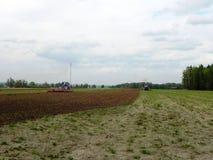 Trattore che ara il campo prima della piantatura della molla Primo piano, paesaggio fotografia stock