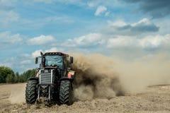 Trattore che ara la terra asciutta dell'azienda agricola all'autunno Fotografie Stock