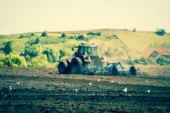 Trattore che ara un campo agricolo Immagine Stock Libera da Diritti