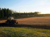 Trattore che ara un campo al tramonto Fotografie Stock Libere da Diritti