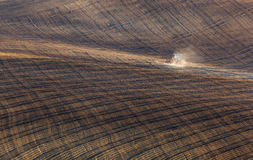 Trattore che ara un campo spogliato in Moravia del sud al tramonto Immagine Stock