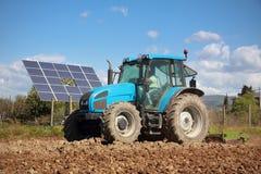 Trattore che coltiva nel campo e nel comitato solare Immagini Stock Libere da Diritti
