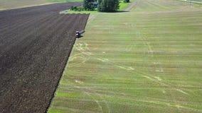 Trattore che coltiva terreno arabile per la semina dei raccolti, stock footage