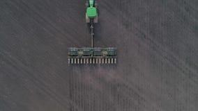 Trattore che coltiva terreno arabile per la semina dei raccolti, vista aerea sul macchinario moderno di agricoltura al campo stock footage