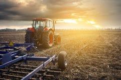 Trattore che funziona nel campo su un fondo di tramonto Fotografia Stock