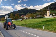 Trattore che guida sulla strada nel villaggio alpino Obermillstatt, Austria Immagine Stock