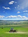 Trattore agricolo che ara e che spruzza sul verticale del campo Immagine Stock Libera da Diritti
