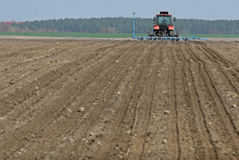 Trattore che prepara terra per seminare Il trattore con il coltivatore tratta il campo prima della piantatura Preparando terra pe Fotografie Stock Libere da Diritti
