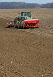 Trattore che prepara terra per seminare Il trattore con il coltivatore tratta il campo prima della piantatura Preparando terra pe Fotografia Stock Libera da Diritti