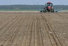 Trattore che prepara terra per seminare Il trattore con il coltivatore tratta il campo prima della piantatura Preparando terra pe Immagini Stock Libere da Diritti