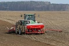 Trattore che prepara terra per seminare Il trattore con il coltivatore tratta il campo prima della piantatura Preparando terra pe Fotografia Stock