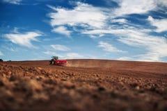 Trattore che semina i raccolti al campo Immagine Stock