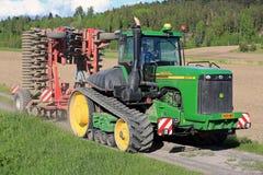 Trattore a cingoli di John Deere 9520T e coltivatore agricoli Fotografie Stock