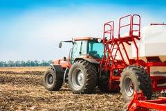 Trattore con i carri armati nel campo Macchinario agricolo e coltivare Immagini Stock Libere da Diritti