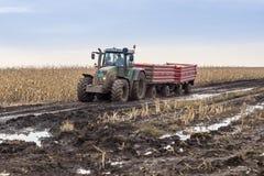 Trattore con i rimorchi nel fango sul campo raccolto Immagine Stock Libera da Diritti