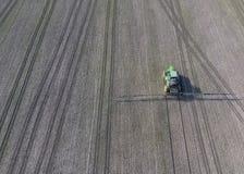 Trattore con il sistema provvisto di cardini degli antiparassitari di spruzzatura Fertilizzando con un trattore, sotto forma di a Immagine Stock