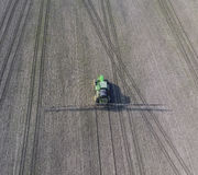 Trattore con il sistema provvisto di cardini degli antiparassitari di spruzzatura Fertilizzando con un trattore, sotto forma di a Fotografie Stock