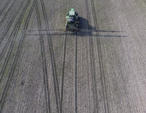 Trattore con il sistema provvisto di cardini degli antiparassitari di spruzzatura Fertilizzando con un trattore, sotto forma di a Immagine Stock Libera da Diritti