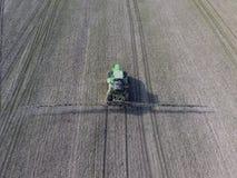 Trattore con il sistema provvisto di cardini degli antiparassitari di spruzzatura Fertilizzando con un trattore, sotto forma di a Immagini Stock Libere da Diritti