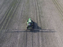Trattore con il sistema provvisto di cardini degli antiparassitari di spruzzatura Fertilizzando con un trattore, sotto forma di a Immagini Stock