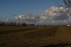 Trattore con l'aratro sul campo del raccolto Campo e trattore di estate TR fotografia stock