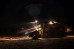 Trattore con le luci sopra alla notte dopo il raccolto della soia Fotografie Stock