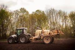 Trattore con lo fertilizzante-spruzzatore del rimorchio sul campo arato Immagine Stock