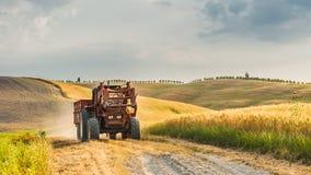 Trattore con un rimorchio sui campi in Toscana, Italia Immagine Stock Libera da Diritti