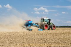 Trattore con una macchina della semina che funziona nel campo Immagine Stock