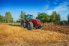 Trattore d'elaborazione agricolo che ara campo dentro Fotografia Stock