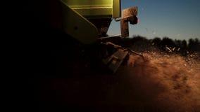 Trattore del primo piano che raccoglie grano alla notte con i fari stock footage