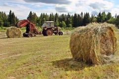 Trattore dell'agricoltore con la pressa per balle che sputa fuori intorno ai rotoli di fieno Immagine Stock