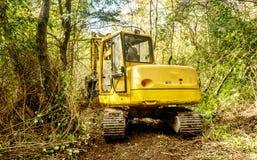 Trattore dell'escavatore che scava un canale per l'acqua nel legno Immagini Stock Libere da Diritti