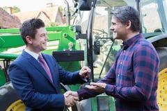 Trattore di Collecting Keys To dell'agricoltore nuovo dall'uomo d'affari Immagini Stock Libere da Diritti