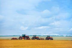 Trattore di giorno di estate tre con l'aratro che sta sul giacimento di grano pendente prima dell'inizio del lavoro Fotografia Stock