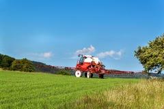 Trattore di spruzzatura del campo Lavoro agricolo su un'azienda agricola in repubblica Ceca Spruzzando contro i parassiti Fotografia Stock Libera da Diritti
