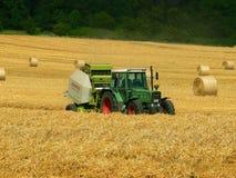 Trattore e campo con grano raccolto in balle Fotografia Stock Libera da Diritti