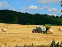 Trattore e campo con grano raccolto in balle Fotografia Stock