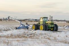 Trattore e caricatore verdi del grano sul campo di neve Fotografia Stock Libera da Diritti