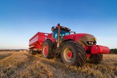 Trattore e rimorchio di agricoltura su un campo di stoppie Fotografia Stock