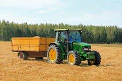 Trattore e rimorchio di Driving John Deere 5820 dell'agricoltore Fotografia Stock