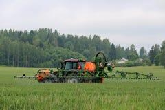 Trattore e spruzzatore montato sul giacimento di grano Fotografia Stock Libera da Diritti