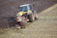 Trattore ed aratro sul lavoro sul campo nella provincia olandese di Flevoland Immagine Stock