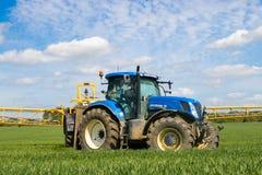 Trattore moderno blu che tira uno spruzzatore del raccolto del rinforzo Immagine Stock Libera da Diritti