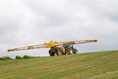 Trattore moderno blu che tira uno spruzzatore del raccolto sulla collina Fotografia Stock