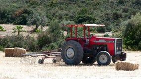 Trattore nel campo che raccoglie i mucchi di fieno, Fotografia Stock