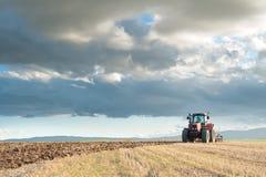 trattore nel campo nella priorità alta con il cielo al tramonto Immagine Stock Libera da Diritti