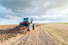 trattore nel campo nella priorità alta con il cielo al tramonto Fotografia Stock Libera da Diritti