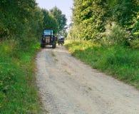 Trattore nella zona rurale, un giro del trattore su una strada della ghiaia verso i ciclisti, turisti Immagini Stock Libere da Diritti